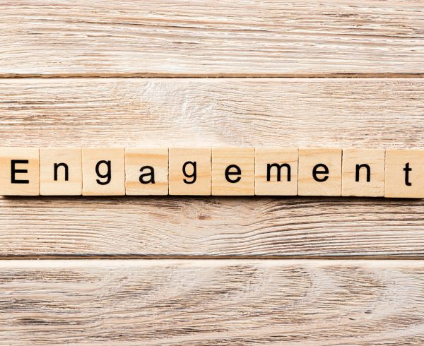 alt=image that displays the word engagement out using scrabble pieces on the background of a wooden panel""