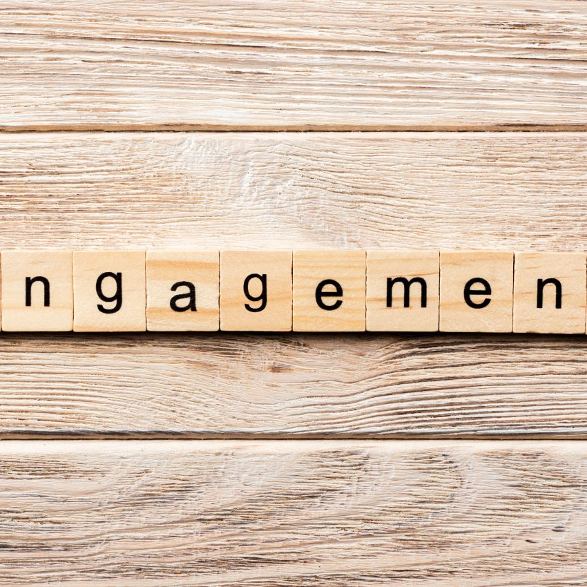 """alt=image that displays the word engagement out using scrabble pieces on the background of a wooden panel"""""""
